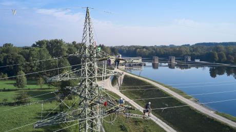 Monteure sind auf einen Strommast am Wasserkraftwerk Ellgau geklettert. Sie erneuern dort die 110-Kilovolt-Stromleitungen.
