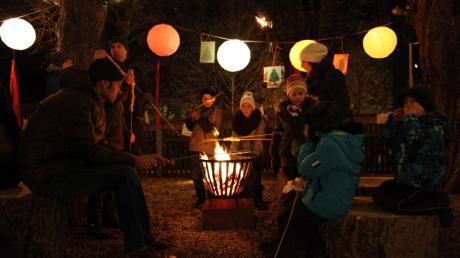 Erwachsene und Kinder genießen beim Stockbrotgrillen am Lagerfeuer die gemütliche Atmosphäre des Haunstetter Weihnachtsmarkts.
