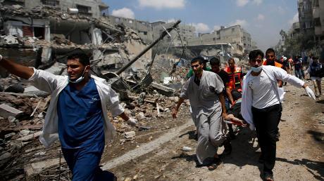 Nach einem Angriff der Israelis im Gazastreifen tragen Palästinenser den Körper eines Mannes davon. Mehr als 500 Menschen starben in den vergangenen Tagen bei den kriegerischen Auseinandersetzungen.