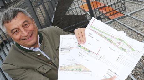 """Sebastian Priller sen. mit den Plänen für seinen """"Bierwalk"""". Er soll künftig Gleis eins des Hauptbahnhofes direkt mit der Brauerei (im Bildhintergrund) verbinden."""