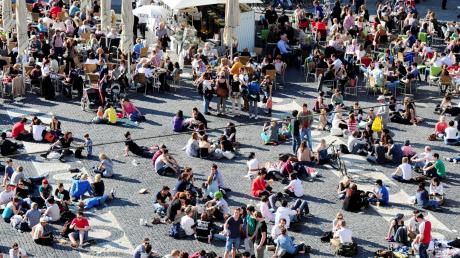 Viele Augsburger zieht es bei Sonnenschein an den Rathausplatz – die Jüngern setzen sich gerne auf den Boden, die älteren Besucher bevorzugen schon eher einen Sitzplatz in einem Lokal.