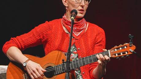 Im geblümten Kleid mit Gitarre auf dem Barhocker: Martina Schwarzmann in der Schwabenhalle.