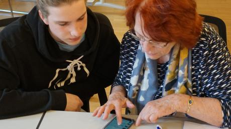 Schüler Moritz Eger hilft Rentnerin Isabella Schuster bei der Erstellung einer Whatsapp-Gruppe.