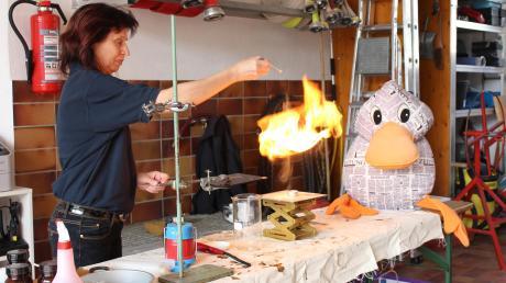 Zeitungsente Paula Print ist mutig und traut sich ganz nah an den Tisch von Brandexpertin Angelika Orner, während sie Holzstaub auf ein brennendes Teelicht träufelt. Das brennt wie Zunder und gibt eine heiße Stichflamme.