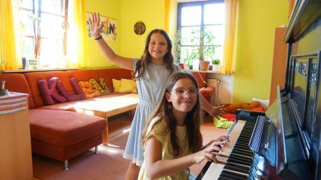 Die neunjährige Kim (links) tanzt im Wohnzimmer der Wohngruppe Villa Kunterbunt des Heims der Kinder-, Jugend- und Familienhilfe Hochzoll, während ihre Freundin Jadranka am Klavier spielt.