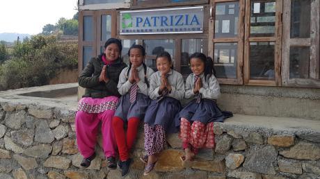 Eine Lehrerin und drei Schülerinnen zeigen ihre Dankbarkeit für die Schule, die mit Unterstützung der Patrizia Stiftung gebaut wurde.