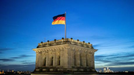 Krisenstimmung in der GroKo: Die Deutschlandfahne weht vor dem Abendhimmel auf dem Reichstag im Wind.