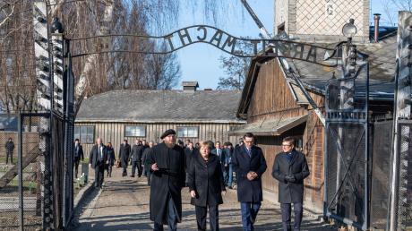Angela Merkel (CDU) geht zusammen mit Polens Ministerpräsident Mateusz Morawiecki (rechts neben ihr), dem Direktor der Gedenkstätte, Piotr Cywinski (links), sowie dem Vizedirektor de Museums Auschwitz-Birkenau Andrzej Kacorzyk durch das Eingangstor des ehemaligen Konzentrationslagers Auschwitz.