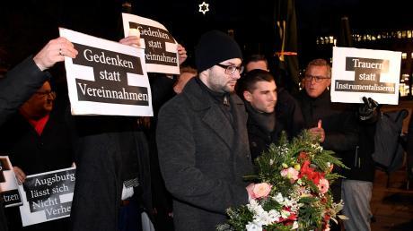AfD-OB-Kandidat Andreas Jurca mit dem Kranz, hinten Gegendemonstranten.