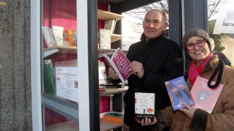 Gregor Lang und die Vorsitzende der Aktionsgemeinschaft Hochzoll, Anne Breidenbach, stöbern in der neuen Telefonbuchzelle neben dem Postgebäude.
