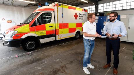 Der neue Geschäftsführer Daniel Freuding (rechts) und Notfallsanitäter Alexander Donderer (stellvertretender Leiter Rettungsdienst und Ausbilder) stehen in der in die Jahre gekommenen Fahrzeughalle der Rettungswache in Günzburg.