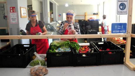 Ehrenamt in Corona-Zeiten: Die Helferinnen der Tafel stehen mit Visier hinter einer schützenden Scheibe.