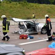 Die Vorderseite eines BMWs blieb auf der Fahrspur nach München liegen. Ein Feuerwehrmann begutachtet das Wrack.