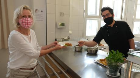 Im Bürgertreff Hochzoll wird der Betrieb langsam wieder hochgefahren. Koch Eugen Ritz händigt Hortleiterin Gudrun Link ein Essen aus.