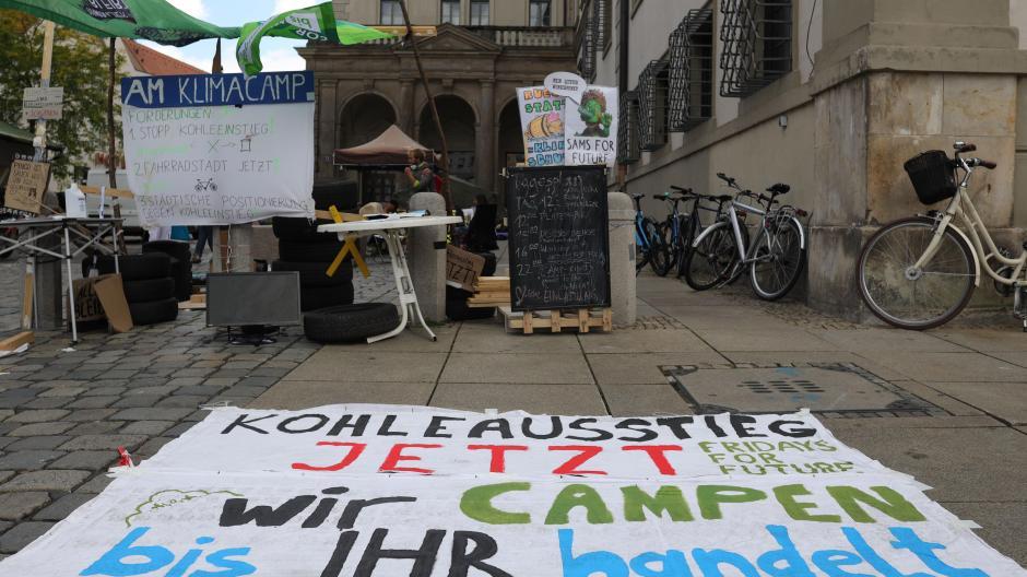 Die Stadt Augsburg will das Klimacamp neben dem Rathaus räumen lassen. Ein Bescheid wurde erlassen, doch vor der Umsetzung will die Stadt auf eine Eilentscheidung des Verwaltungsgerichts warten.