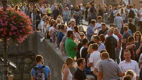 Menschen, die sich zum Feierabend auf ein Glas Wein treffen. So sah es vor Corona im Sommer oftmals auf der Alten Mainbrücke aus.
