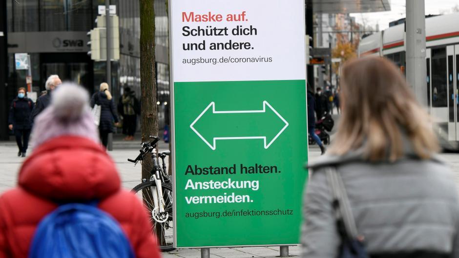 Große Schilder weisen am Königsplatz in Augsburg auf die Corona-Regeln hin.