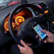 Die Nutzung des Handys am Steuer ist verboten. Strafen drohen selbst dann, wenn Autofahrer das Telefon bloß in die Hand nehmen. Foto: Monika Skolimowska
