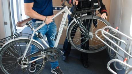 Ein Fahrgast verstaut sein Fahrrad in einem ICE 4, während ihm eine Zugführerin dabei hilft. Foto: Andreas Gebert/dpa