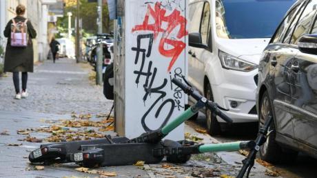 E-Scooter liegen auf einem Gehweg.