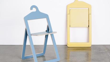 Stühle sind ja oft Kleiderfänger. Dieser hier hat sogar die richtige Ablagefläche - im Hanger Chair von Philippe Malouin für die Marke Umbra Shift verbinden sich die Funktionen Klappstuhl und Kleiderbügel.