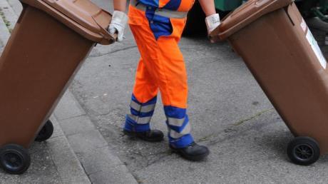 Ein Mitarbeiter der Abfallwirtschaft und Stadtreinigung schiebt eine braune Tonne mit Biomüll zum Müllwagen. Foto: Patrick Seeger/Illustration