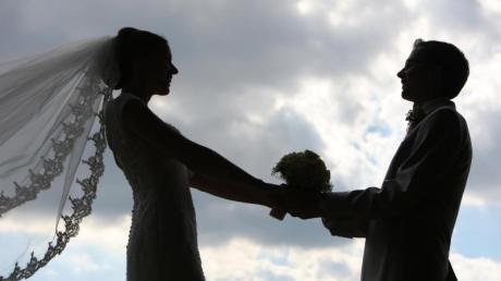 Die Silhouette eines frisch vermählten Hochzeitspaares zeichnet sich im Gegenlicht ab.