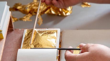 Eine Arbeit, die viel Konzentration und Fingerspitzengefühl erfordert: In der Blattgoldschlägerei Eytzinger im fränkischen Schwabach werden mit Ebenholzstäben die Blattgoldseiten in die Hefte von Hand eingelegt.