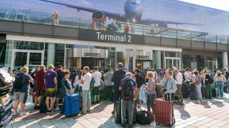Zahlreiche Menschen standen am Dienstag wegen eines verdächtigen Fluggastes vor dem verschlossenen Eingang zum Terminal 2 am Münchner Flughafen im Außenbereich.