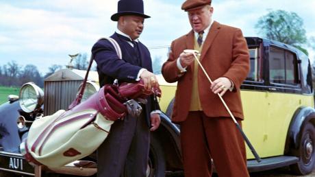 """Film-Bösewichte: Auric Goldfinger, gespielt von Gert Fröbe (rechts), und sein Leibwächter Oddjob (Harold Sakata). Gibt es in der Realität auch """"Goldfinger""""-Bösewichte? Oder war das Steuergestaltungsmodell legal?"""