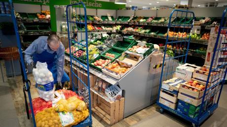 Ein Mitarbeiter füllt Kartoffeln, Zwiebeln und Obst in einem Supermarkt auf. Viele Verbraucher sorgen sich, ob es davon in den kommenden Wochen genug geben wird.