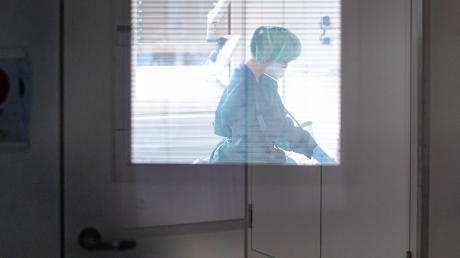 Hinter der Tür herrscht Dauerstress: Eine Krankenschwester auf der Infektionsstation einer Klinik.