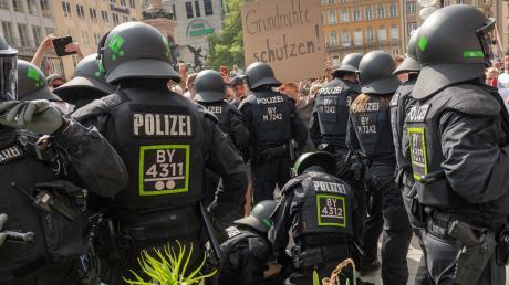 Polizisten ringen eine Demonstranten auf den Boden, der zuvor in einer Menschenansammlung auf dem Marienplatz demonstriert hat.