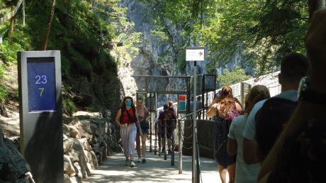 Urlaub mit Maske: Touristen an der Marienbrücke bei Schloss Neuschwanstein – nebst digitaler Besucher-Zählsäule.