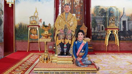König Maha Vajiralongkorn im Juli 2019 auf seinem Thron in Bangkok. Zu seinen Füßen Zweitfrau Sineenat Wongvajirapakdi, die er kurz danach verstieß, nun aber wieder begnadigt hat.