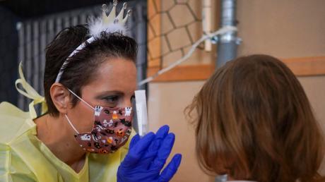 Gegenüber Kindern sollte man beim Thema Corona besonders einfühlsam sein: Hier testet eine italienische Krankenschwester ein Mädchen alsPrinzessin verkleidet.