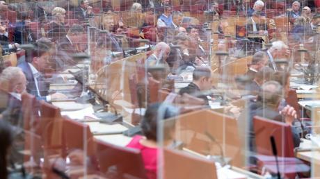 Wenn die Abgeordneten im Bayerischen Landtag zusammenkommen, verfolgen sie die Debatten hinter solchen Plexiglasscheiben.