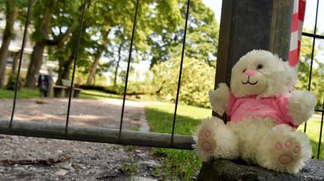 Der Spielplatz ist jetzt abgesperrt, jemand hat ein Kuscheltier abgelegt: Am Samstag fiel ein Baum auf diesem Spielplatz in Augsburg auf eine Mutter und ihr Kind.