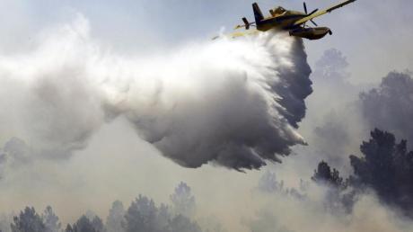 Ein Löschflugzeug verteilt im portugiesischen Vila Velha de Rodao entlang des Tajo eine Ladung Wasser. Fast 2000 Feuerwehrleute sind bei sechs großen Waldbränden im Einsatz. Foto: Armando Franca