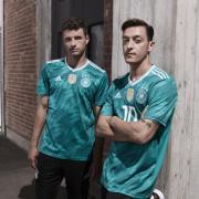 Alles auf Grün: Die Weltmeister Thomas Müller (l) und Mesut Özil präsentieren das neue Auswärtstrikot der DFB-Elf. Foto: adidas /dpa
