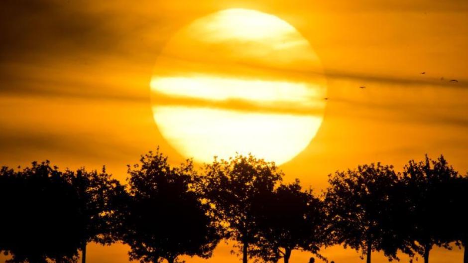 Am Kronsberg in Hannover zeichnen sich die Silhouetten von Passanten vor der abendlichen Sonne ab. Foto: Julian Stratenschulte