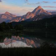 Der in der Abendsonne liegende Tegelberg (l.) und der Säuling (r.) spiegeln sich im Weißensee in Bayern. Foto: Karl-Josef Hildenbrand