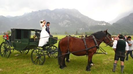 Ein chinesisches Brautpaar posiert vor dem Schloss Neuschwanstein bei Hohenschwangau auf einer Pferdekutsche für die Fotografen.