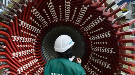 Eine Frau betrachtet einen Generatorständer im Siemens-Generatorenwerk in Erfurt.