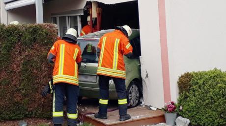 Einsatzkräfte der Feuerwehr stehen an einem Auto, das durch eine Hauswand gefahren war.