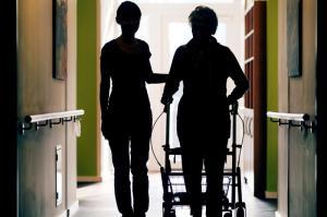 Eine Pflegekraft (l) begleitet die Bewohnerin eines Altenheims beim Gang über den Flur. Laut BA sind im Jahresdurchschnitt 2018 in der Altenpflege auf knapp 3100 arbeitslose Fachkräfte rund 15.300 freie Stellen entfallen. Foto: Oliver Berg