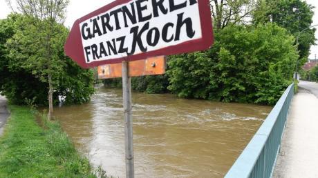 Im Günzburger Stadtteil Wasserburg ist die Günz nach Hochwasser teilweise ausgeufert. Das Flussbett ist bis zur Oberkante voll.