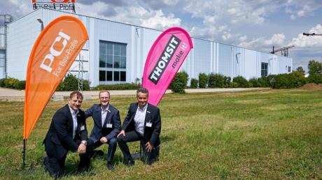 Die Unternehmensleitung mit Frank Rösiger, Marc C. Köppe und Holger Sommer (von links) kniet auf der Grünfläche, auf der das neue Lieferzentrum entstehen soll.