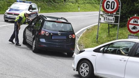 Hier geht's nicht weiter: Ein Polizist hält Autos auf einer Straße bei Innsbruck an. Foto: Zeitungsfoto.At/Daniel Liebl/APA