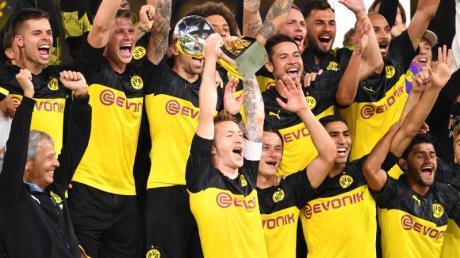 Dortmunds Marco Reus (M) bejubelt mit seinem Trainer Lucien Favre (l) und Mitspielern den Gewinn des Supercups 2019.